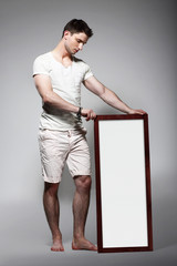 Shoeless Man Displaying White Board with Blank Space