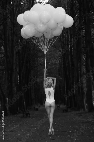 Melancholy. Lonely Woman with Balloons in Dark and Gloomy Forest © gromovataya