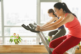 Young women on stationary bikes exercising in the gym
