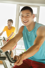 Young men on stationary bikes exercising in the gym