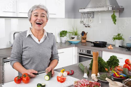 Seniorin - ältere Frau hat Spaß beim Kochen - Gemüse