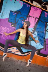 Teenage girl with gray hat dansing in front of graffiti wall