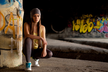 Teenage girl with gray hat in front of graffiti wall