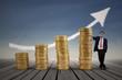 Asian businessman standing next to gold coins chart