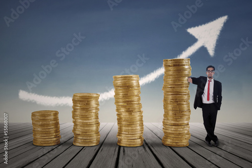 Asian businessman standing next to gold coins chart