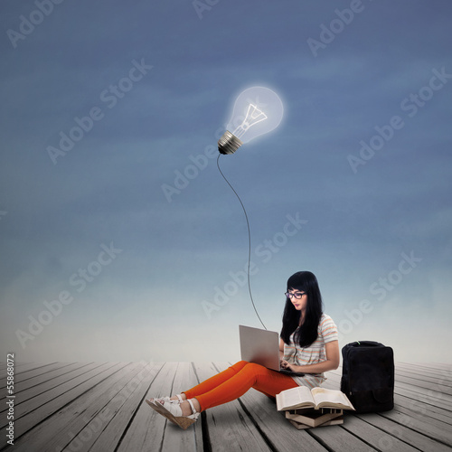 Asian female student typing on laptop under lit bulb