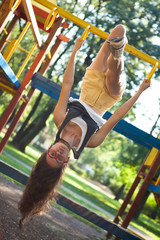 Young woman in the playground upside down