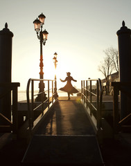 silhouette of the girl dancing on the bridge, against rising