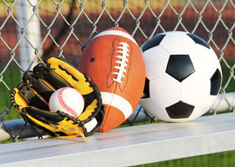 Sports balls. Soccer ball, football, baseball in glove. Outdoors