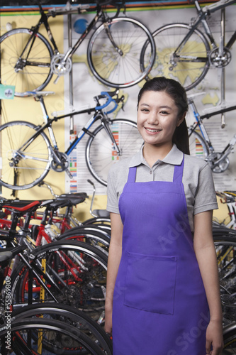 Portrait of young female mechanic in bicycle store, Beijing
