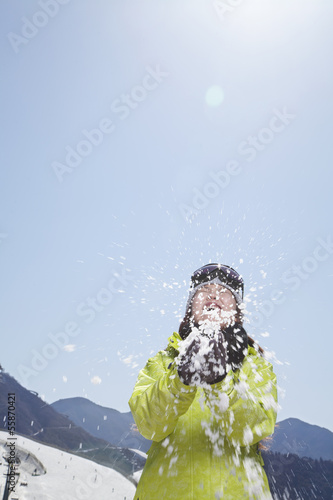 Young Woman Playing with Snow in the Mountains