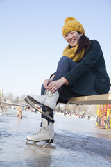 Young Woman Tying Ice Skates Outside