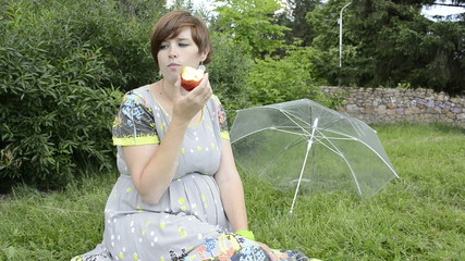 Pregnant woman eating apple sitting on the grass