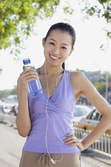 Young Woman with Bottled Water Listening to Music