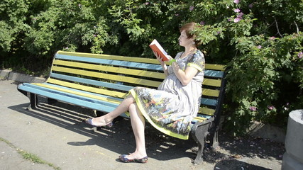 Pregnant woman reading book on the bench