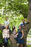 Five young friends around a tree