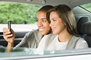 Young couple using a cellular phone in car