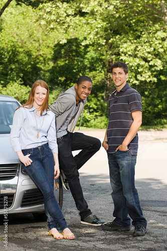 Three young friends with a car
