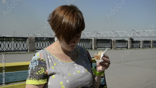 Pregnant woman on the waterfront eating sandwich