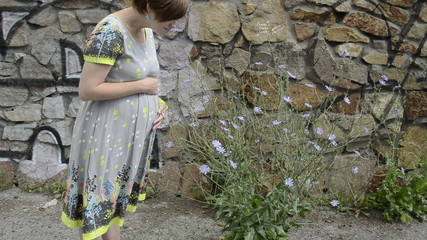 Pregnant girl smelling flower near the wall