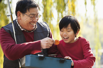 Grandfather and grandson looking at fishing tackle box
