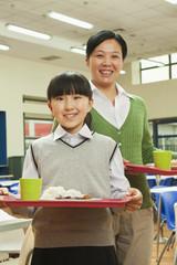 Teacher and school girl portrait in school cafeteria