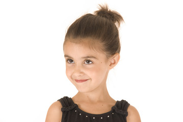 young girl in black leotard with sparkly eyes head tilted smilin