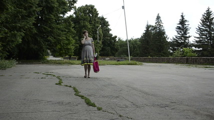 Young pregnant woman is walking in a park with bag and umbrella