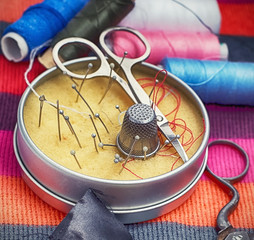 Round box of needles and scissors