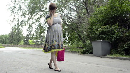 Young pregnant woman is walking in a park talking on the phone
