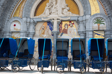 Loans of blue wheelchairs in front of the church within the Sanc