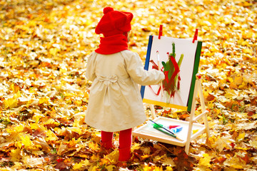 Child drawing on easel in Autumn Park. Creative kids development