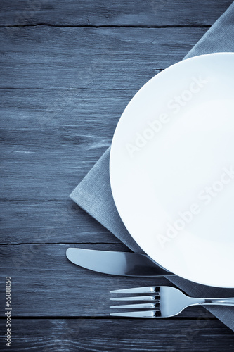 white plate, knife and fork on wood