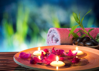 dish spa with floating candles, orchid, bambu towel in garden