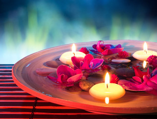 dish spa with floating candles, orchid, in garden