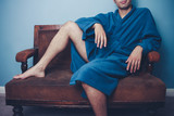 Young man in robe posing on vintage sofa