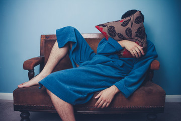 Man in dressing gown sleeping with face behind cushion
