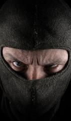 Masked man on a dark background