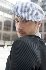 Fashion portrait of handsome man in check cap