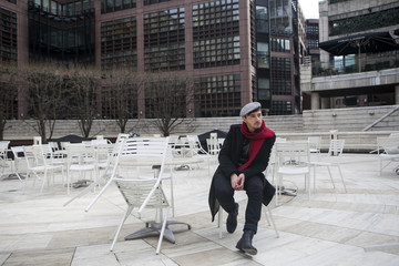 sad man wearing check cap red scarf sitting at  street cafe