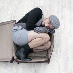 pensive man in check cap lying in broken trunk