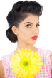 Thoughtful black hair model holding a flower and looking at came