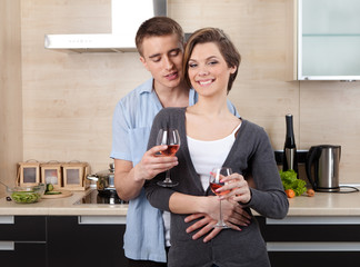 Couple with goblets hugs one another
