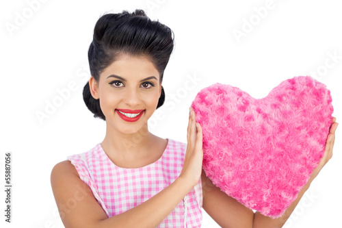 Lovely black hair model holding a pink heart shaped pillow