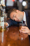 Drunk businessman holding whiskey glass lying on a counter