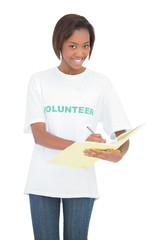Smiling volunteer woman writing on notebook