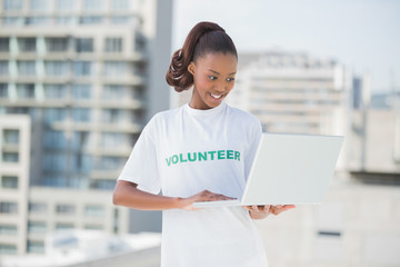 Happy volunteer using laptop