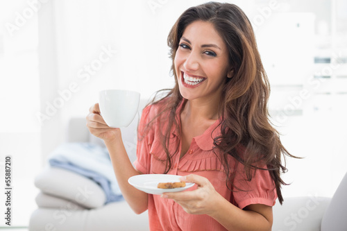Happy brunette sitting on her sofa holding cup and saucer