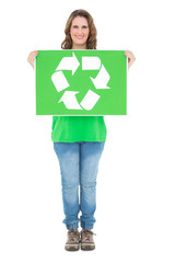 Smiling environmental activist holding recycling sign looking at