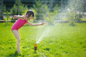 Girl running though a sprinkler